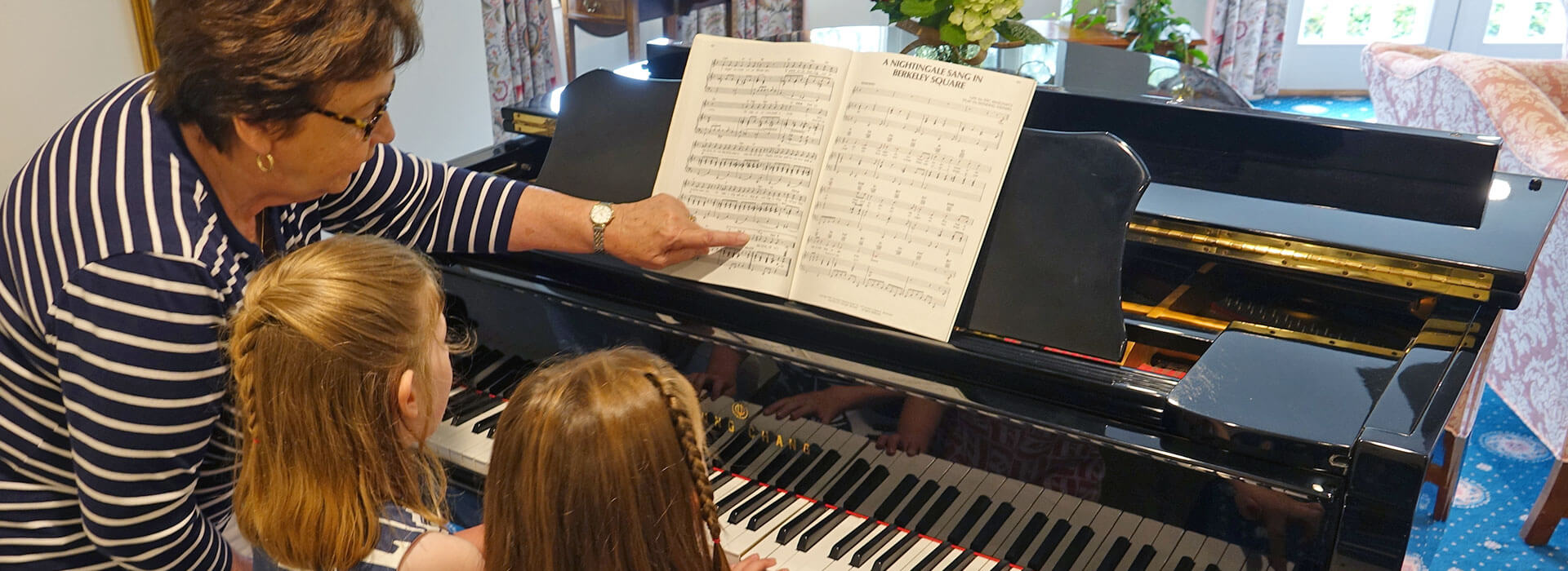 woman teaching her granddaughters the piano